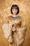 美丽的埃及妇女喜欢有香水瓶的帕特拉在金黄背景 免版税库存图片