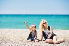 美丽的基于海滩的妇女和她迷人的女儿 免版税库存图片