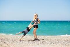 美丽的基于海滩的妇女和她迷人的女儿 免版税图库摄影