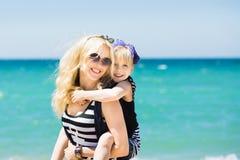 美丽的基于海滩的妇女和她迷人的女儿 免版税库存照片