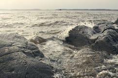 美丽的夏季具体照片 大冰砾和岩石与风雨如磐/风大浪急的海面和波浪一起 可爱的光和 免版税库存照片