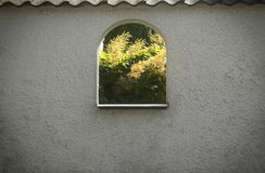 美丽的夏季具体照片 有好的纹理和字符的白色混凝土墙和显示好漂亮的东西或人的被删去的窗口 图库摄影