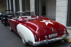 美丽的大红色经典汽车在哈瓦那街道停放了 库存图片