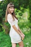 年轻美丽的夫人在一个绿色公园在夏天 免版税库存图片