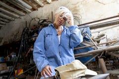 美丽的夫人在工作在他的老车间 免版税库存照片