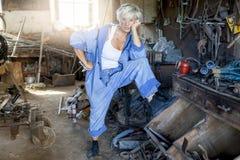 美丽的夫人在工作在他的老车间 免版税图库摄影