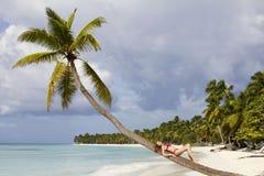 美丽的夫人坐棕榈树在热带海滩 免版税库存照片