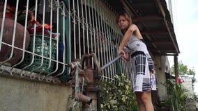 美丽的夫人抽从一个深井手扶的水泵的水 股票视频