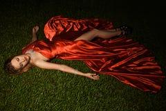 美丽的夫人In Red在草的Dress Lying 库存照片
