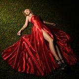 美丽的夫人In Red在绿草的Dress Lying 图库摄影