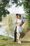 美丽的夫妇拥抱年轻人 免版税图库摄影