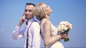 美丽的夫妇新婚佳偶 站立支持,新郎微笑,调查照相机,反对背景 股票录像