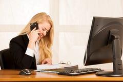美丽的女商人在一个巧妙的电话谈话在她的办公室在 免版税库存照片