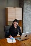 美丽的女商人坐椅子与片剂和膝上型计算机一起使用在办公室 免版税库存照片