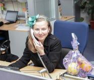 美丽的女商人谈话在电话在她的书桌在办公室 免版税库存图片