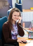 美丽的女商人谈话在电话在她的在offi的书桌 免版税库存照片