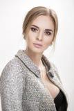美丽的女商人金发碧眼的女人画象黑礼服的,在灰色背景的夹克 免版税图库摄影