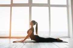 年轻美丽的女子实践的瑜伽和体操 健康概念 在唯一体育的类 库存照片