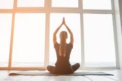 年轻美丽的女子实践的瑜伽和体操 健康概念 在唯一体育的类 库存图片