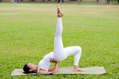 美丽的女子实践的瑜伽在公园 库存图片