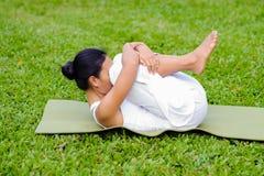 美丽的女子实践的瑜伽在公园 免版税库存图片