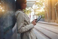 美丽的女学生通过便携式的数字式片剂搜寻信息在互联网 库存图片