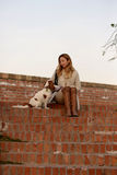 美丽的女孩与她的狗骑士国王查尔斯狗坐红砖台阶 免版税库存图片