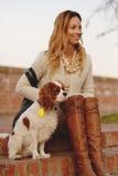 美丽的女孩与她的狗骑士国王查尔斯狗坐红砖台阶 库存照片