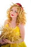 美丽的女孩与小麦耳朵的穿戴的黄色 免版税库存照片