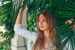 美丽的女孩与棕榈叶的一个假期 免版税库存图片