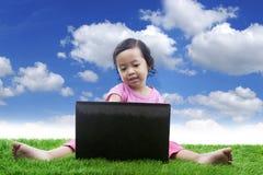 美丽的女孩与笔记本坐草甸 免版税图库摄影