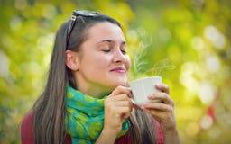 美丽的女孩享用一份咖啡本质上 库存照片