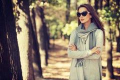 美丽的女孩以时髦的时尚在秋天公园穿衣 图库摄影