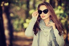 美丽的女孩以时髦的时尚在秋天公园穿衣 免版税库存照片