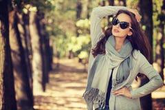 美丽的女孩以时髦的时尚在秋天公园穿衣 库存照片
