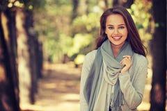 美丽的女孩以时髦的时尚在秋天公园穿衣 免版税图库摄影