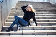 美丽的女孩佩带的白色帽子,黑hoody,鞋子和牛仔裤 图库摄影