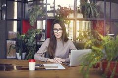 美丽的女孩佩带的眼睛玻璃在coworking的演播室 使用膝上型计算机和智能手机在木桌上 青年人w的概念 免版税库存照片