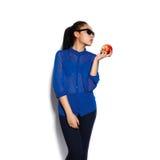 美丽的女孩佩带的玻璃用一个苹果在一只手上在白色背景 免版税库存图片