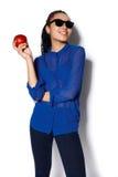 美丽的女孩佩带的玻璃用一个苹果在一只手上在白色背景 免版税图库摄影