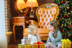 美丽的女孩使用与坐与礼物的地板 免版税库存图片