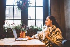 美丽的女孩使用膝上型计算机技术,类型看在咖啡馆的文本显示器由窗口在木桌 免版税图库摄影