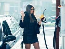 美丽的女孩倾吐了燃料入坦克车 免版税库存图片