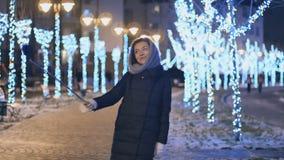 美丽的女孩做一selfie在夜光背景在冬天 股票录像