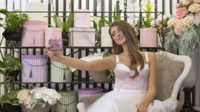 美丽的女孩做在花店的selfie 影视素材