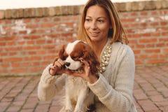 美丽的女孩做心脏对她的狗骑士国王查尔斯狗在红砖台阶 免版税库存照片