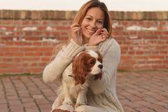 美丽的女孩做鹿耳朵对她的狗骑士国王查尔斯狗在红砖台阶 免版税库存照片