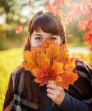 美丽的女孩关闭秋天槭树花束离开的面孔 库存图片