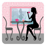 美丽的女孩剪影在咖啡馆坐 免版税库存照片