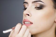 美丽的女孩化妆师绘嘴唇 特写镜头 库存照片